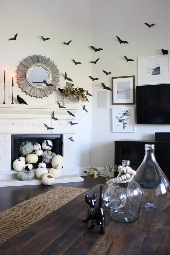 black paper bats covering the fireplace and the wall, natural pumpkins in the fireplace, black candles and blackbirds for Halloween