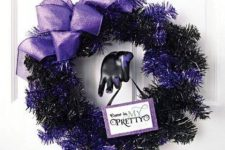 15 a black and purple Halloween wreath with a large purple bow and a sign is a lovely idea for styling your front door