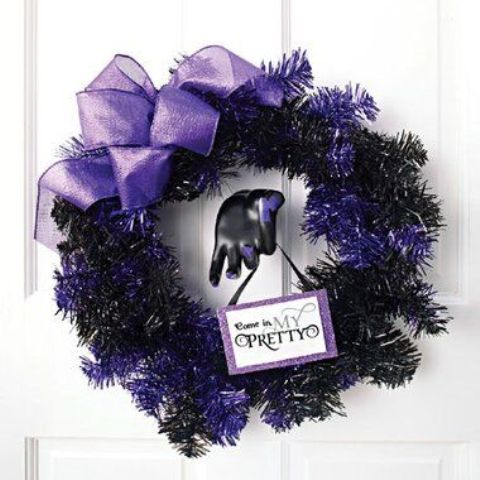 a black and purple Halloween wreath with a large purple bow and a sign is a lovely idea for styling your front door