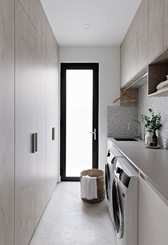 a narrow laundry room with neutral plywood cabinets and a tile backsplash plus a narrow frosted glass door that lets light inside