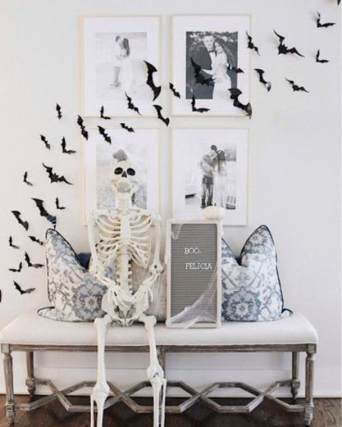 an entryway bench with printed pillows, a skeleton, a grid gallery wall and black paper bats on it is a cool idea