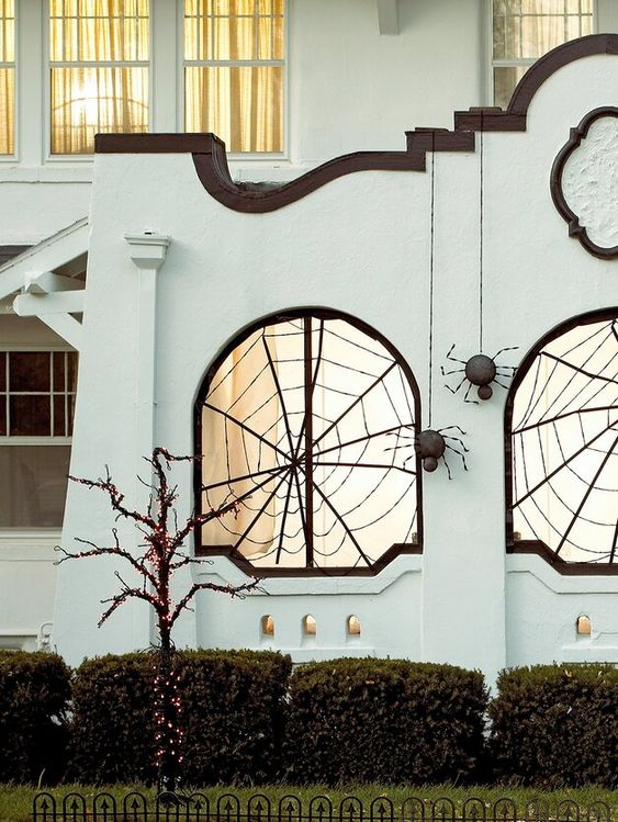 outdoors styled with black spiderwebs and black spiders hanging down is a cool idea for Halloween and looks wow