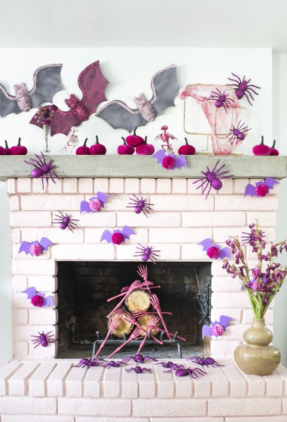 a bright Halloween fireplace with fuchsia pumpkins, pink spiders and lilac bats, large grey and pink bats on the wall