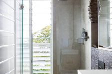 16 a contemporary bathroom clad with tan tiles, with a shower space enclosed in glass and a floor to ceiling window with frosted glass