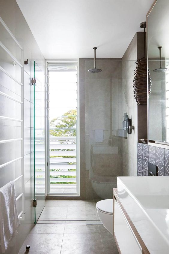 a contemporary bathroom clad with tan tiles, with a shower space enclosed in glass and a floor to ceiling window with frosted glass