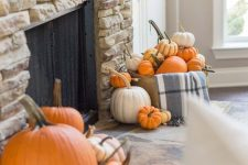 16 a faux stone fireplace with bright faux and real pumpkins in front of it is a cool idea for the fall and is easy to realize