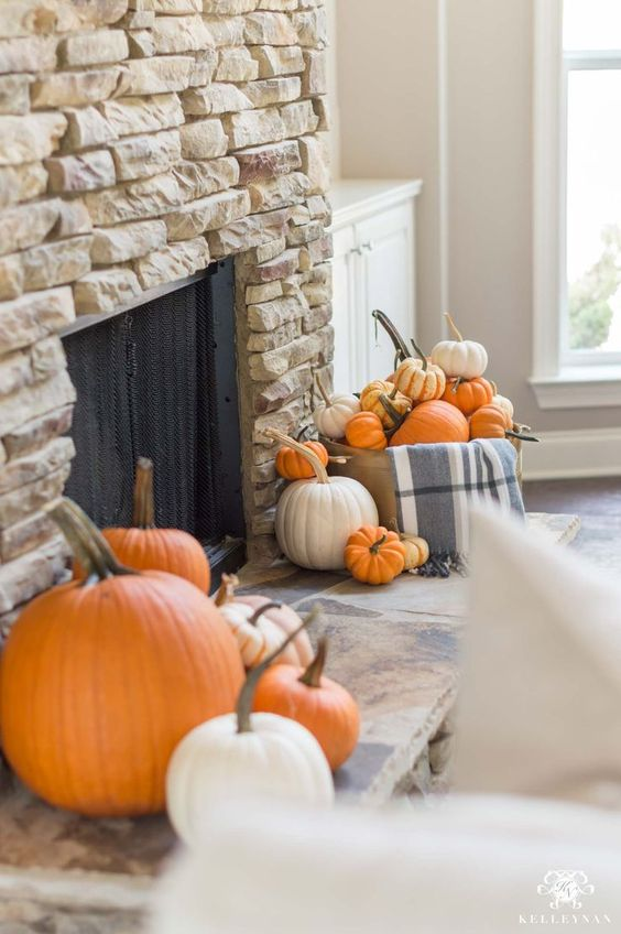 a faux stone fireplace with bright faux and real pumpkins in front of it is a cool idea for the fall and is easy to realize