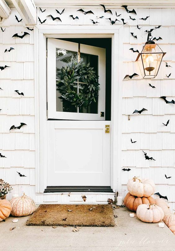 a white farmhouse with black paper bats covering the walls, heirloom pumpkins stached and some fall leaves is awesome