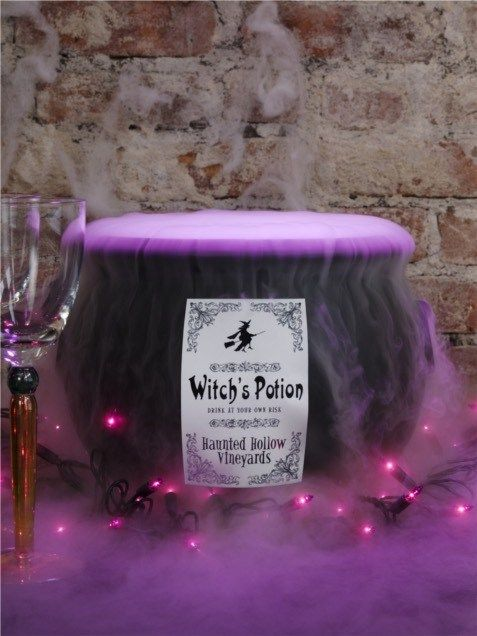 a cauldron with purple lights and purple smoke is a cool idea for Halloween decor for a bold touch