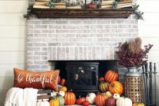 17 a hearth surrounded with colorful faux pumpkins, berries and branches, a bold pillow and some books and pumpkins on the mantel