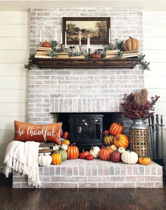 a hearth surrounded with colorful faux pumpkins, berries and branches, a bold pillow and some books and pumpkins on the mantel