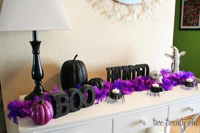 a cool console table with a purple faux fur garland, a purple glitter pumpkin and a black one plus letters for Halloween