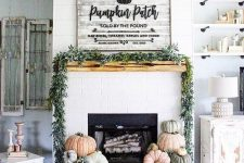 18 a lovely farmhouse fireplace with lots of heirloom pumpkins stacked, a greenery garland on the mantel and a large pumpkin sign