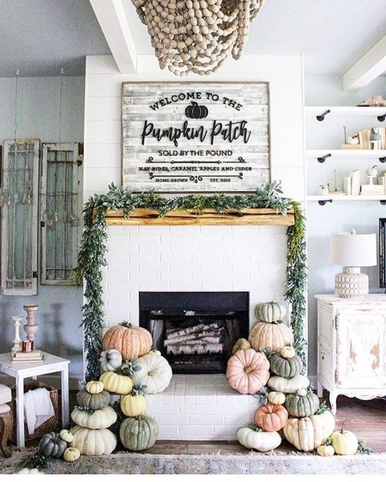 a lovely farmhouse fireplace with lots of heirloom pumpkins stacked, a greenery garland on the mantel and a large pumpkin sign