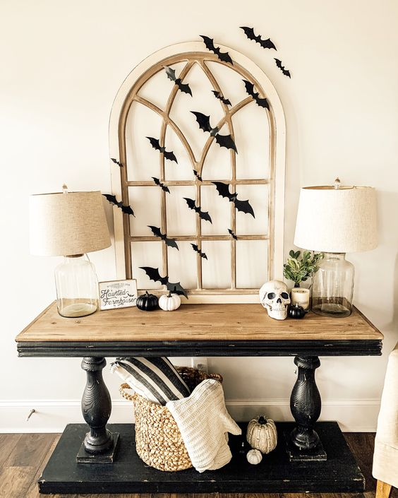 a stylish rustic vintage console table with black and white pumpkins, a skull, a vintage window frame and black paper bats covering it