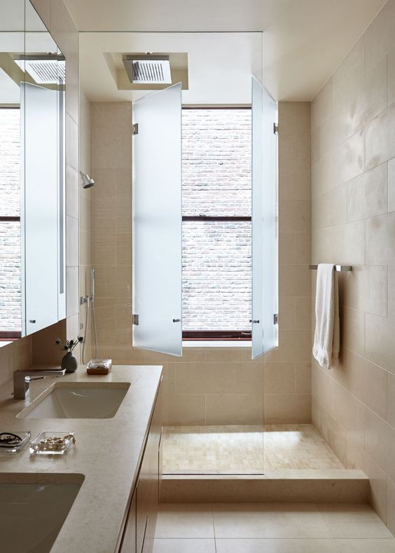 a tan colored bathroom with a shower space and a large window covered with blue frosted glass to let the light in still