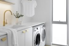 18 an all-white laundry room with a narrow floor to ceiling frosted glass window that lets light inside and makes the space cozier