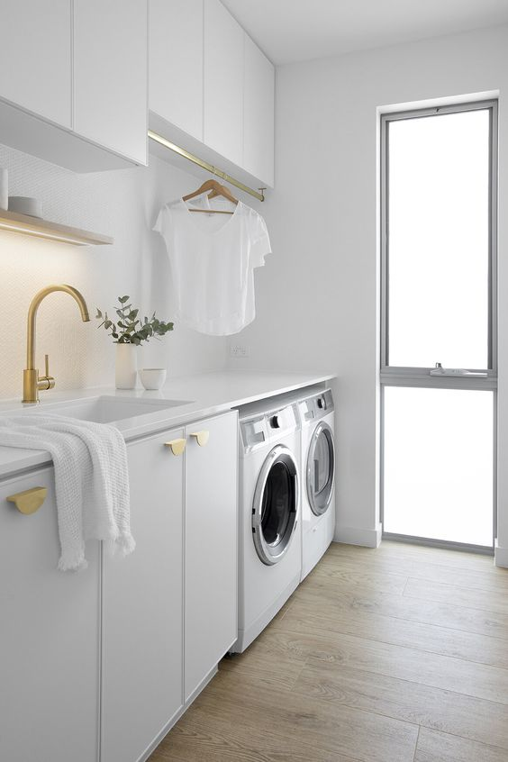 an all white laundry room with a narrow floor to ceiling frosted glass window that lets light inside and makes the space cozier