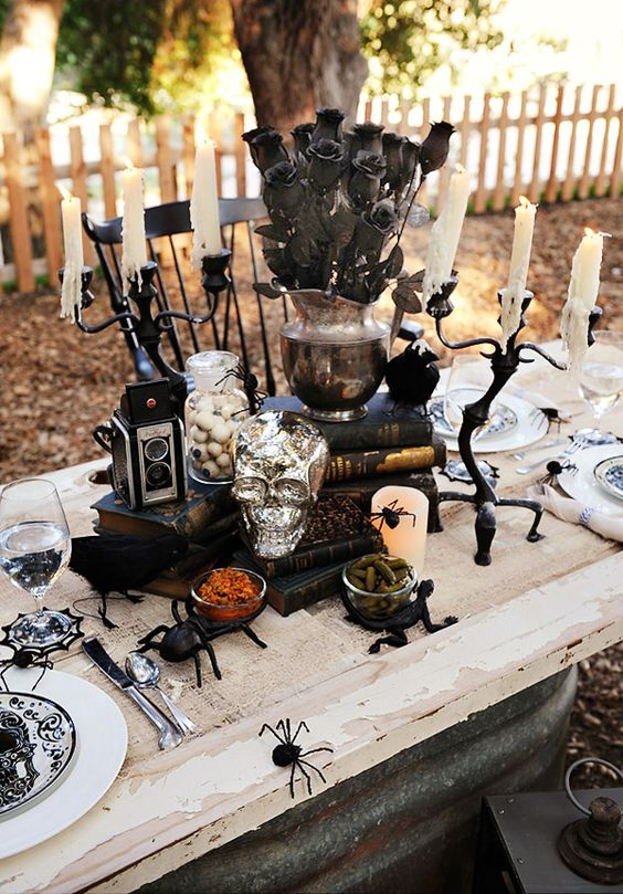 a bold Halloween tablescape with black and white porcelain, black candelabras, books, skulls, black flowers and black spiders for a scarier feel