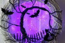 19 a gorgeous glowing Halloween wreath of whitewashed vine, black bats and cats, a black bottle cleaner tree and purple lights is breathtaking