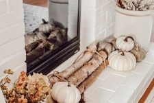 19 a lovely neutral rustic fireplace with firewood, heirloom pumpkins, dried blooms and leaves in buckets is a cool idea