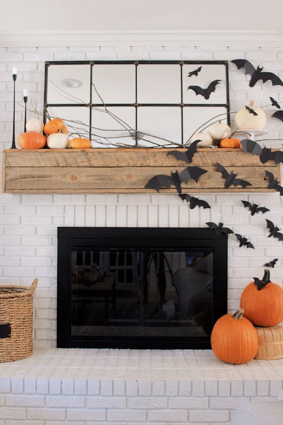 a rustic Halloween fireplace with orange pumpkins on the mantel, branches, black paper bats on the fireplace and wall