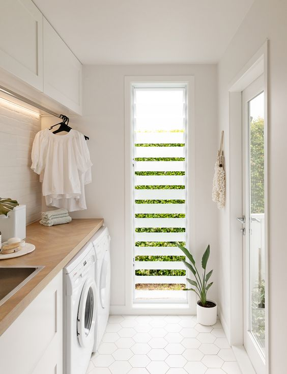 a stylish contemporary laundry in neutrals, with hex tiles on the floor and a shutter window of frosted glass for ventilatin and privacy