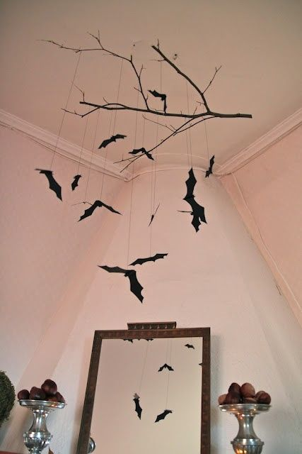 a black branch with bats hanging down is a cool and very easy decoration for Halloween that you can easily DIY