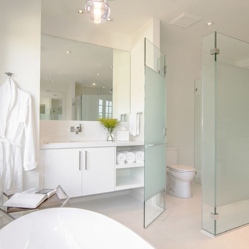 a blue frosted glass toilet partition for more privacy and even a slightly colored touch to the neutral space