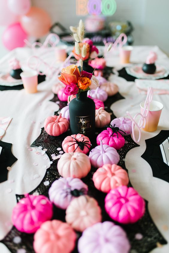 a bright pink Halloween party tablescape with a black table runner, pink and peachy pumpkins, black spiders and a black vase with dried and faux blooms