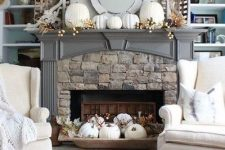 20 a rustic fall fireplace with a bowl with white pumpkins and leaves, white pumpkins and berries on the mantel plus baskets