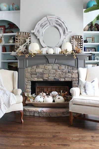 a rustic fall fireplace with a bowl with white pumpkins and leaves, white pumpkins and berries on the mantel plus baskets