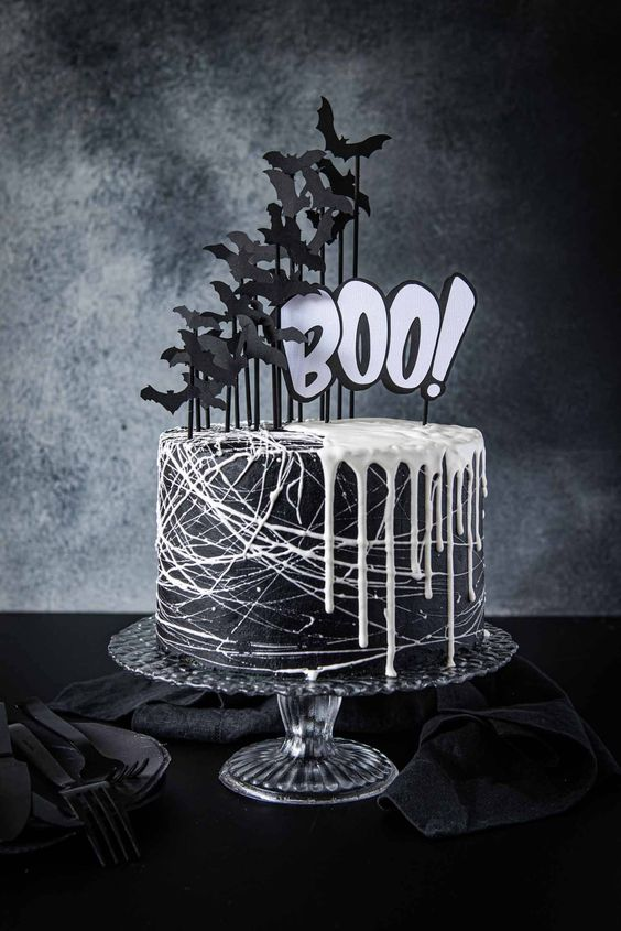 a black Halloween cake with white drip and lots of black paper bats and white letters is a gorgeous idea to go for
