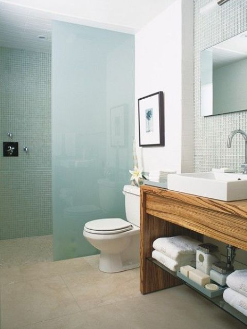 a contemporary bathroom with a shower space done with blue tiles and blue frosted glass that separates the shower and gives privacy to this space