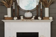 21 a rustic fall fireplace with a sign, white and vine pumpkins, wheat and grasses in vases, candles and pumpkins on the mantel