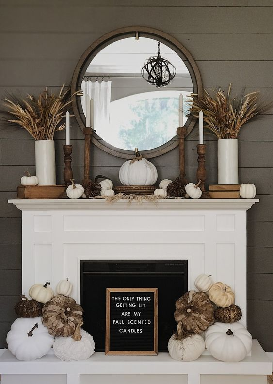 a rustic fall fireplace with a sign, white and vine pumpkins, wheat and grasses in vases, candles and pumpkins on the mantel