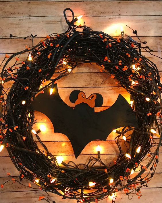 a black vine Halloween wreath with lights, orange blooms, a large black paper bat is a cool solution to DIY easily