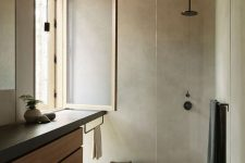 22 a neutral bathroom of concrete, with light-stained wood, a window with a stained frame and clear glass – no privacy here
