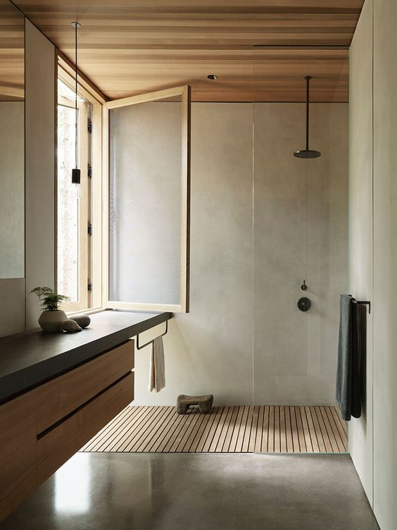 a neutral bathroom of concrete, with light stained wood, a window with a stained frame and clear glass   no privacy here
