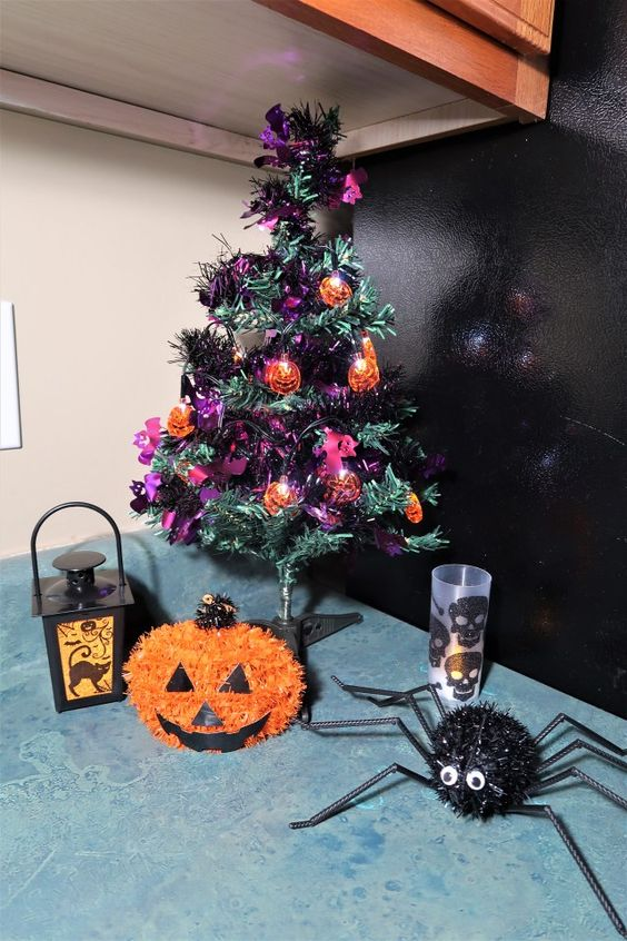 a purple and green tabletop Halloween tree with lights and ornaments is a cool decor idea that you can DIY