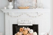 22 a white brick fireplace with white and pastel pumpkins, blooms, a garland and some branches on the mantel is great for the fall