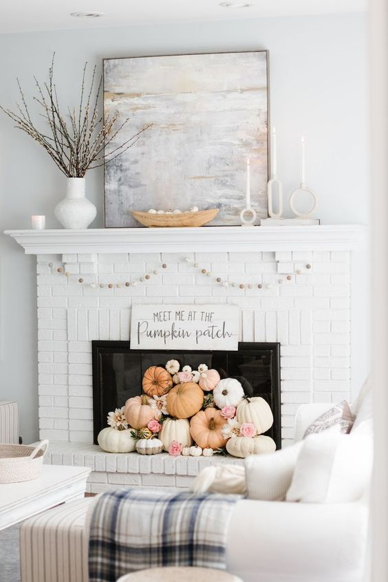 a white brick fireplace with white and pastel pumpkins, blooms, a garland and some branches on the mantel is great for the fall