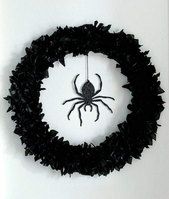 a black faux flower wreath and a black glitter spider is a stunning solution for decorating your front door and it looks elegant