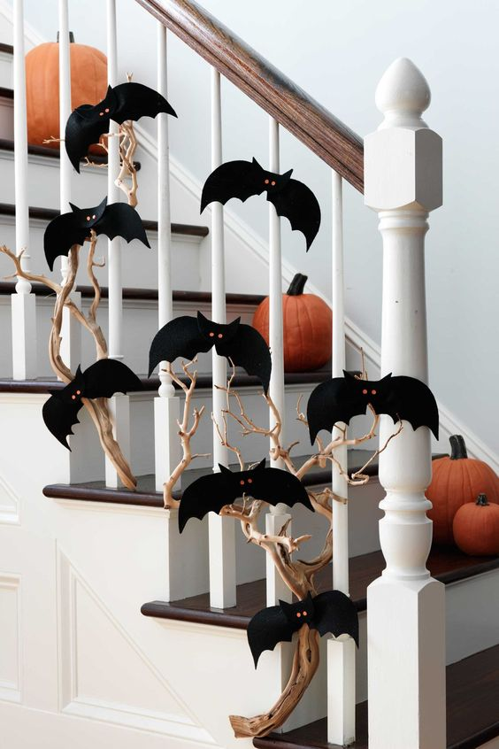 a branch covered with black paper bats with red eyes and pumpkins on the steps to style the space for Halloween easily