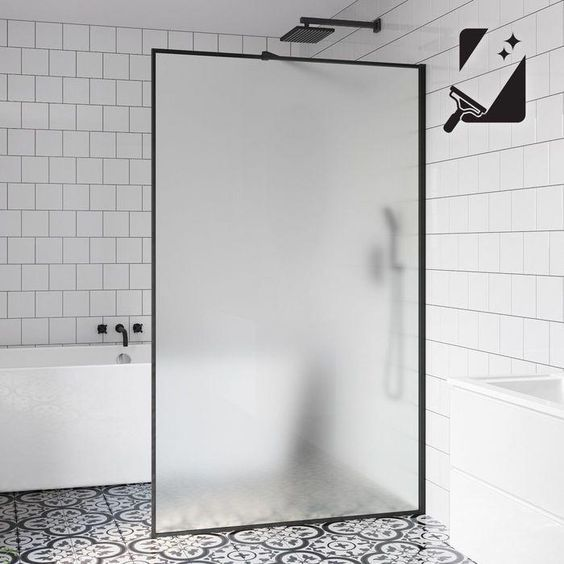 a contemporary black and white bathroom with two types of tiles and a frosted glass divider that keeps water in the bathing zone