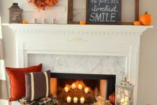 23 bright fall fireplace styling with candles, printed pillows and a blanket next to it, a crate with pumpkins and leaves plus a bold wreath and pumpkins