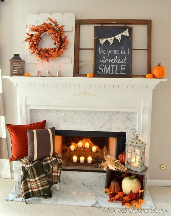 bright fall fireplace styling with candles, printed pillows and a blanket next to it, a crate with pumpkins and leaves plus a bold wreath and pumpkins