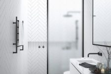 24 a contemporary black and white bathroom with white chevron and black printed tiles, a frosted glass space divider and a skylight over the shower