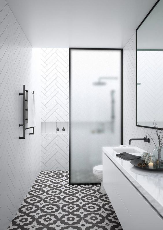 a contemporary black and white bathroom with white chevron and black printed tiles, a frosted glass space divider and a skylight over the shower