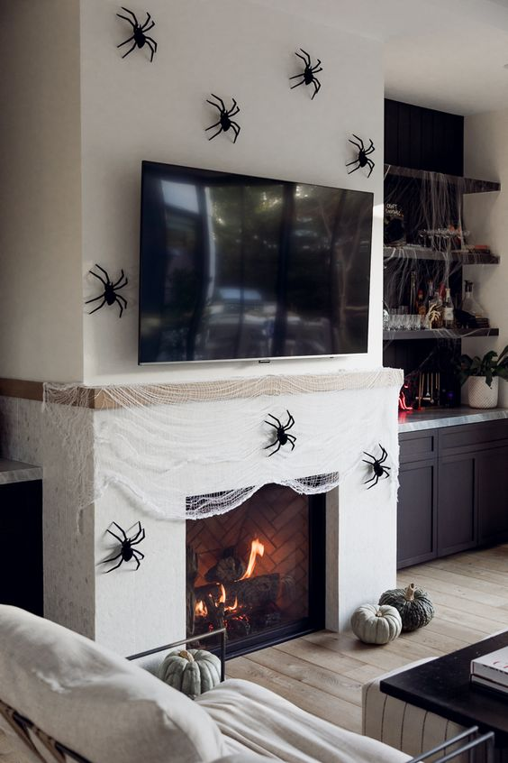 a fireplace covered with faux spiderweb and black spiders, a couple of heirloom pumpkins is a gorgeous idea for Halloween